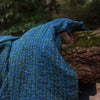 Kantha Home indigo throw in blue green displayed on a tree branch