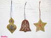 Three metal Christmas ornaments on a white wood background. The first ornament is a brass bauble with blue stitching, the second ornament is a copper bell with white stitching, and the third ornament is a brass star with red stitching.