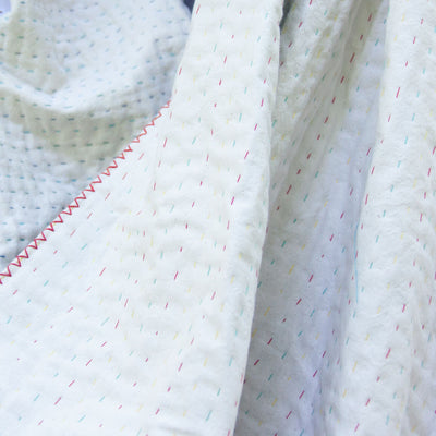 Natural White, a natural Kantha throw with red stitching available at Kantha Home