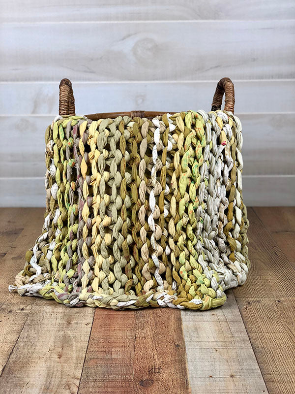 Kantha Home's Natural Chunky Knit Throw made by Basha features tan, white, and green strips of sari cloth hand lumed together to make a beautiful fair-trade Kantha blanket that is displayed in a wicker basket against a white background on a wooden floor