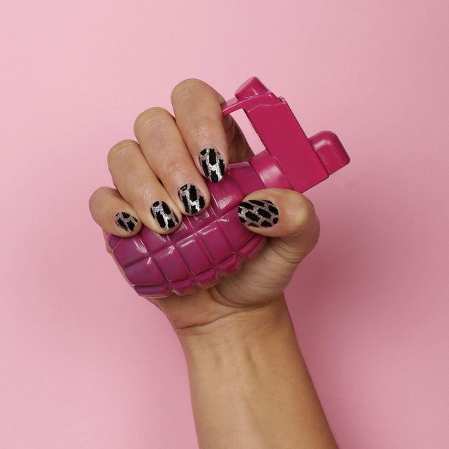Hand holding pink grenade with bomb pattern glitter nail wrap pattern