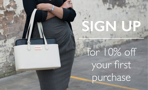Corporate woman holding a hand bag with her arms crossed. Sign up discount 10% off first purchase