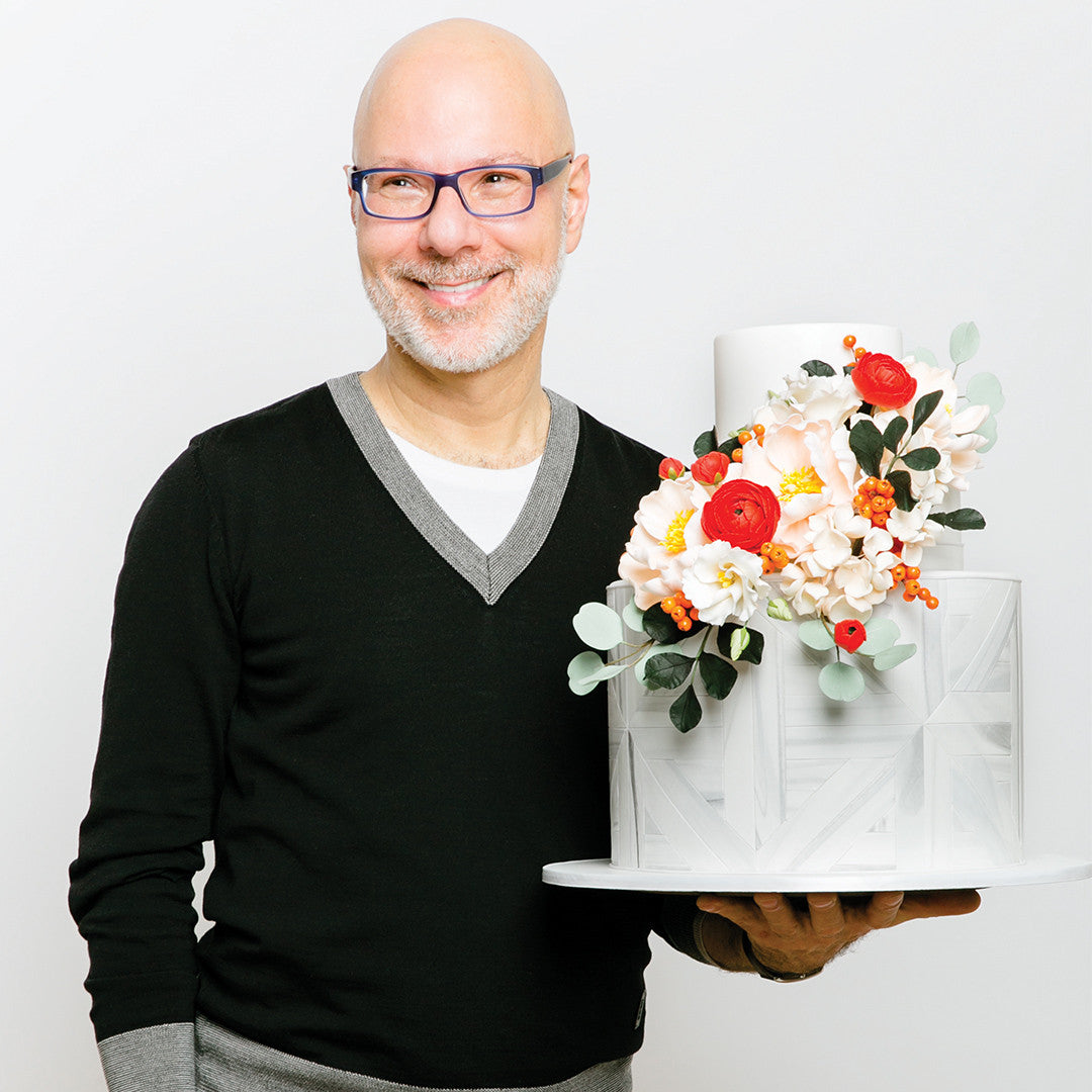Wedding cake guru Ron Ben-Israel poses with his spiced wedding cake topped with magnificent sugar flowers!