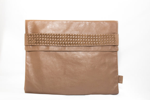 The case can be closed with a flap which tucks into the leather woven strap, holding everything in place.