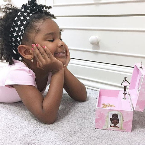 Black Girl Looking at her Nia Ballerina Jewelery Box with Love