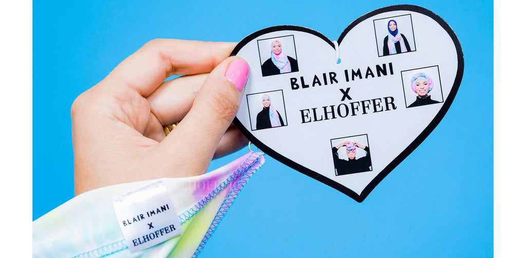 Blair Imani holds the tag for the Blair Imani X Elhoffer Design scarf collaboration. The tag is a white heart with black outline featuring the text of Blair Imani X Elhoffer in the center and 5 photos of Blair wearing the light pink and light blue head scarf.