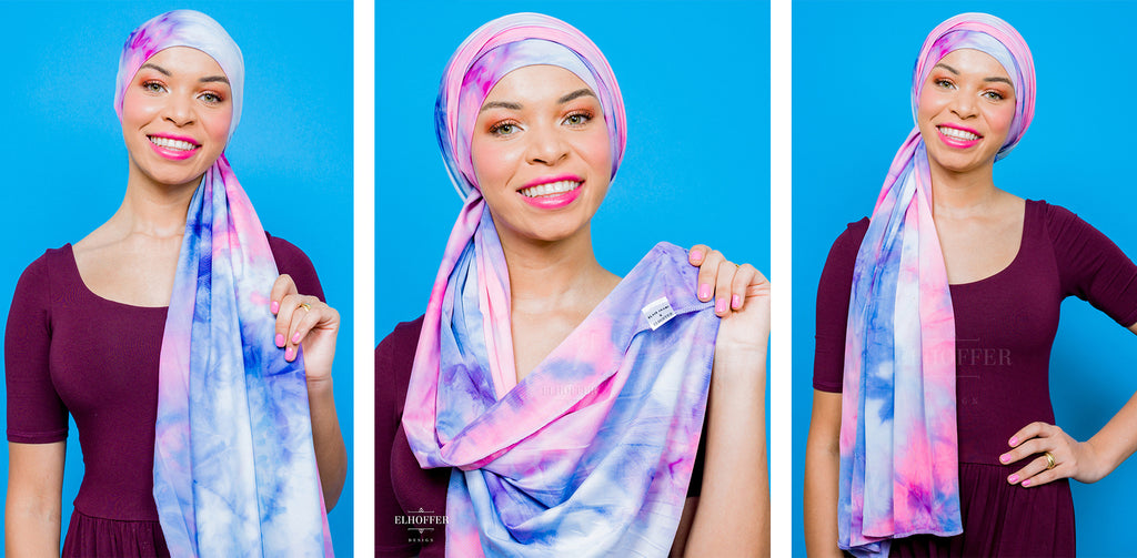 Blair (a medium skinned hijabi model) wears the pink, blue, and white tie dyed scarf as a hijab, covering her hair and draped over her shoulder.