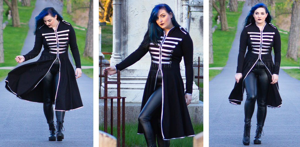 Christina-Marie (a fair skinned size M model with black and blue long hair) models the Dark Parade Tunic. The tunic is all black with long sleeves and falls below the knees, and has silver vinyl trim and military style button accents on the front.