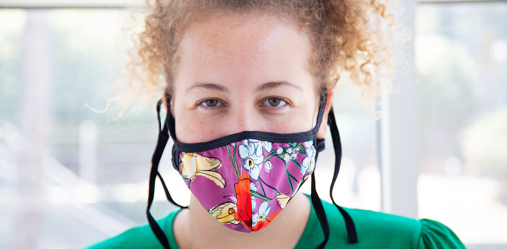 Anastasia, a medium fair skinned model with curly blonde hair, models the California Dreaming Face Cover. The face cover's pattern has a purple base with purple, yellow, and orange flowers. The hem and ties for the face cover are black.