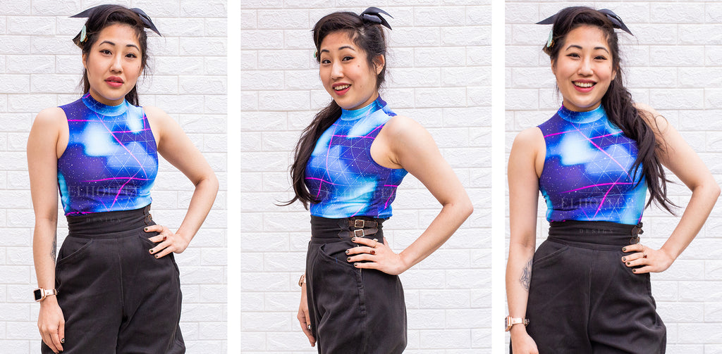 Kate (a medium fair skinned model with long dark hair in a ponytail) models the Jes Crop Top in the Forcefield print. The Jes Crop is a sleeveless spandex top that falls to the natural waist and has a mock turtleneck. The Forcefield print is a blue, purple, and white cloudy print with a white and pink laser styled triangles.
