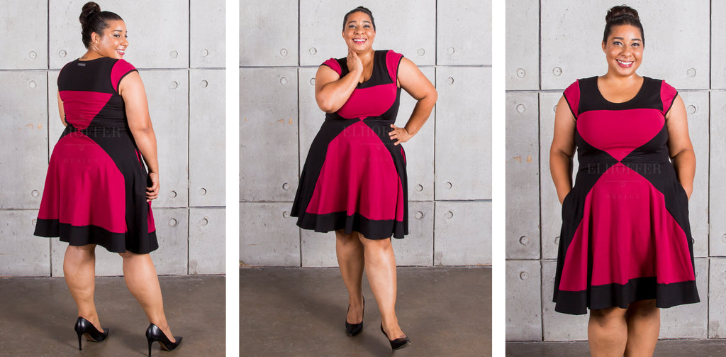 Janae (a medium dark skinned model with dark hair in a bun) models the cap sleeve knee length dress. The dress has red cap sleeves, a red hourglass shape on the front and back, and the rest of the dress is black.