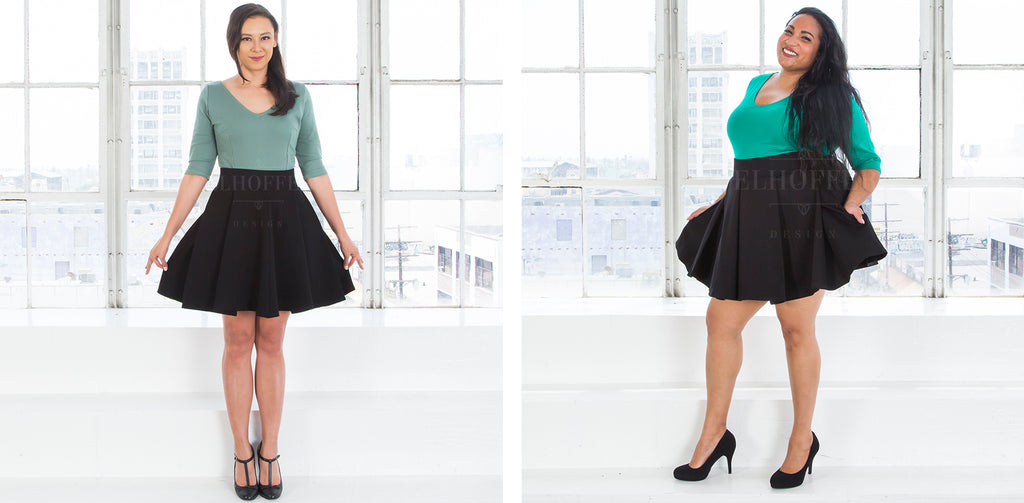 On the left, Kim (a medium fair skinned size small model with brunette hair) models the above the knee pleated black skirt with pockets and pairs it with a sage green v-neck 3/4 sleeve top. On the right, Tas (a medium skinned size 2X model with long dark hair) models the black above the knee skirt with a thick waistband and pockets and pairs it with a kelly green v-neck, 3/4 sleeve top.