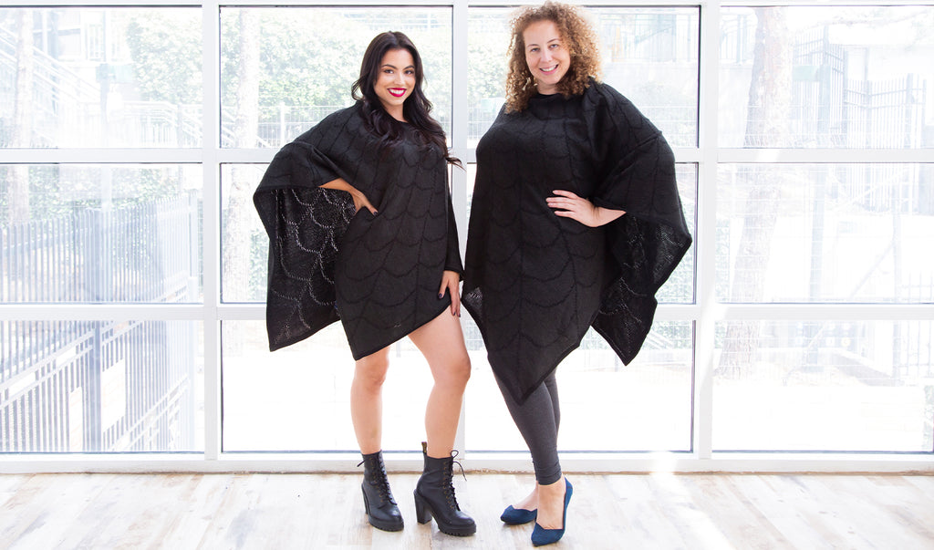 Andrea (a medium skinned size XS model with long dark hair) and Anastasia (a medium light skinned size XL model with blonde curly hair) model the Strange and Unusual Poncho in Dark Vibes. The poncho is dark charcoal grey with a black spiderweb pattern. It falls in a v hem to their knees.