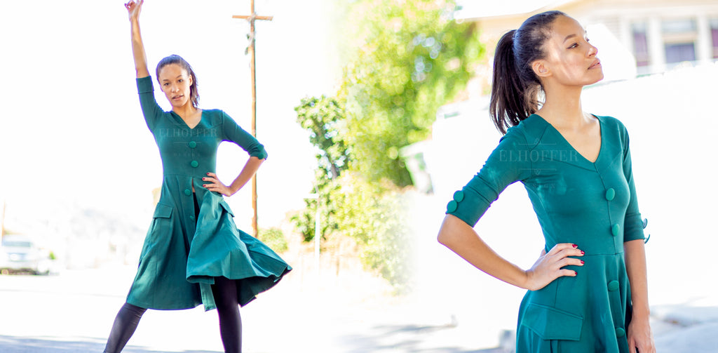 Vanessa models the green Alexander Hamilton inspired tunic outside, with her right fist raised in the air.