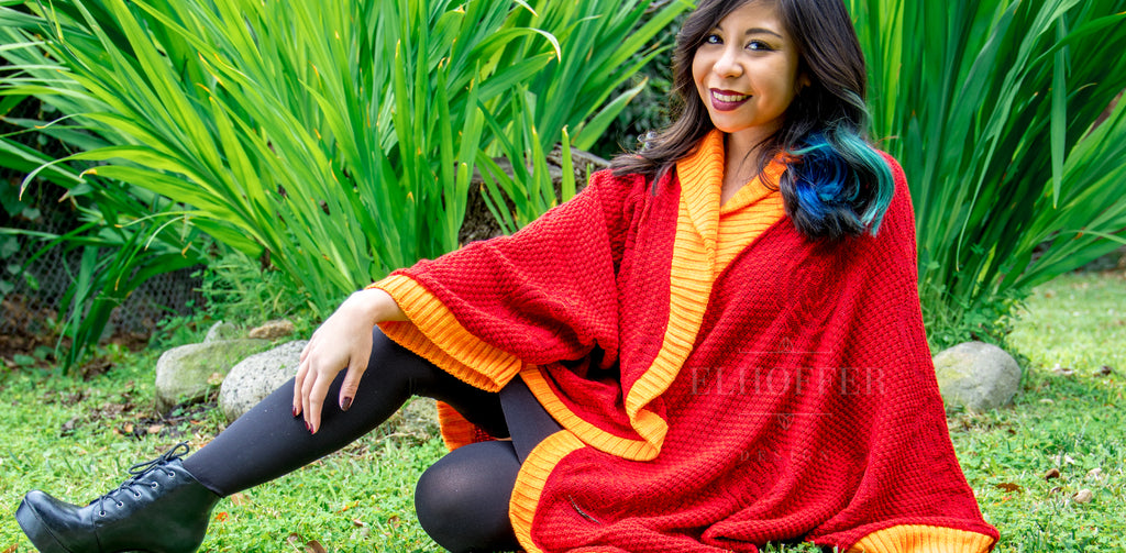 Melanie, a medium light skinned model with dark hair, models the Galactic Appeal Dolman. The dolman is a bright red textured knit with orange cuffs and hems.
