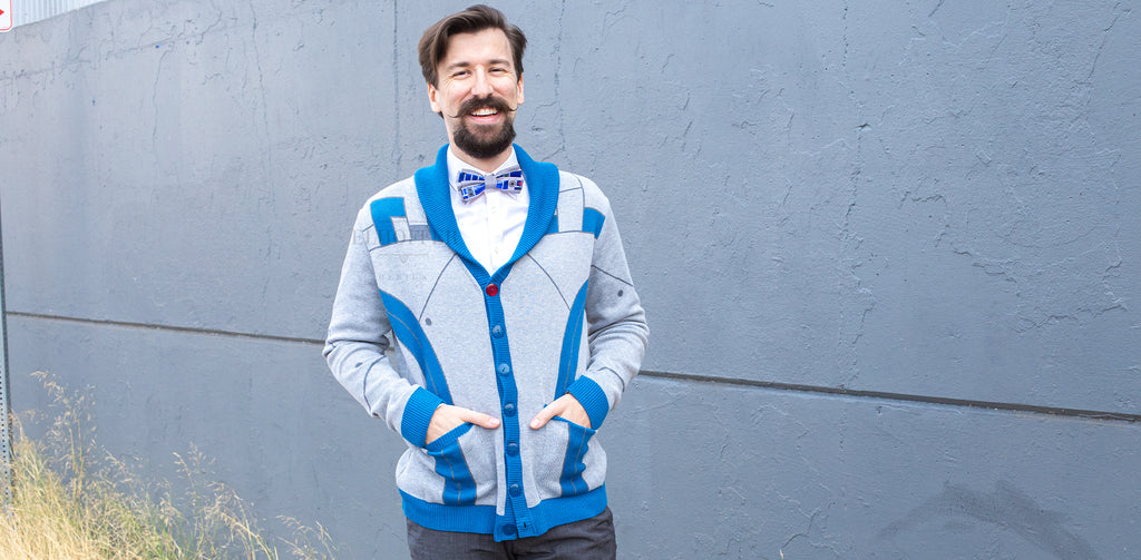 A male model wears the Baby Bot Shawl Collar Cardigan, pairing it with a white button down and bow tie.