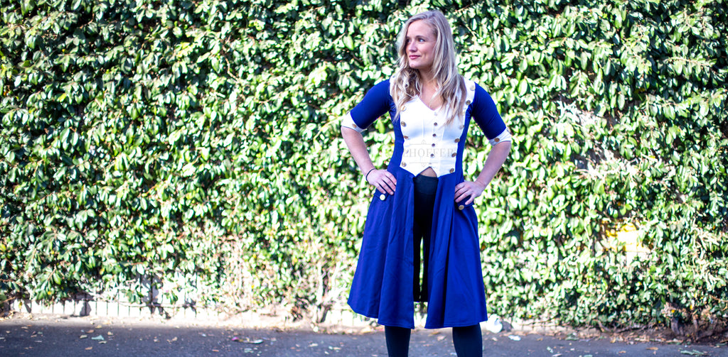 A blonde model wears a blue revolutionary war inspired tunic and black leggings in front of a background of green leaves.