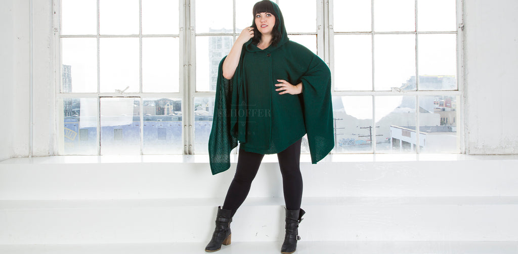 The model is wearing the hunter green Galactic Scavenger Cape, paired with leggings and boots.