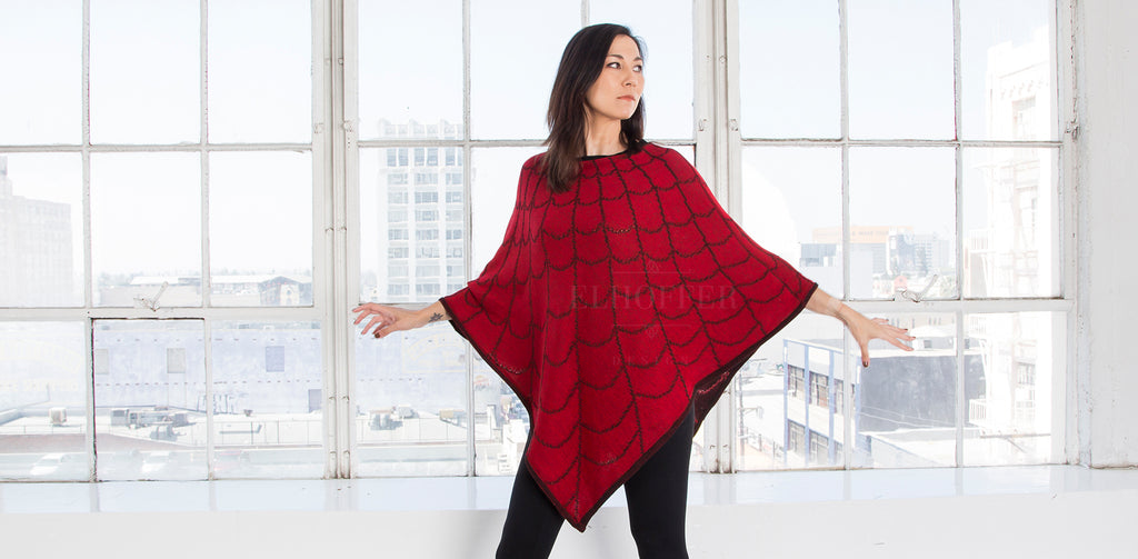 Susan, a medium fair skinned model with dark hair, wears the Strange and Unusual Poncho. The poncho is red with a black spiderweb pattern and has a triangle hem that falls below the knee.