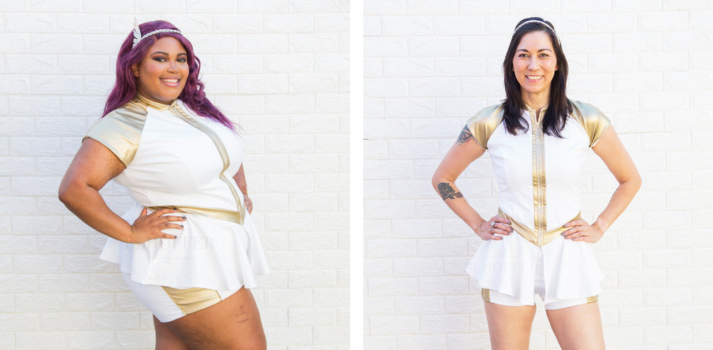 On the left, Jade (a medium dark skinned size 2X model with purple hair) and on the right, Susan (a medium fair skinned size XS model with dark hair), model the Peplum of Power and Hotpants of Power. The Peplum is a white zip front top with a high neck and short sleeves. the sleeves, zipper, and pointed waistband are gold vinyl and the white peplum hem falls to the top of the thighs. The hotpants are short white shorts with gold vinyl side stripe over the pockets.