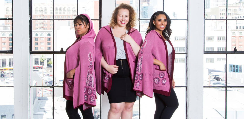 The models are wearing the Galactic Princess Cape Longline Cardigan. It is a pink hooded open front cardigan with open wing sleeves with a design on them.