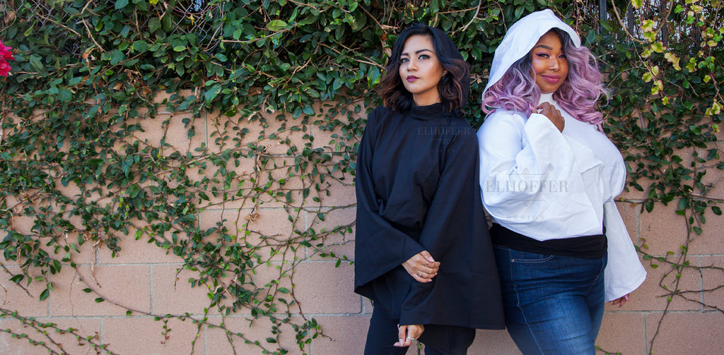 The models wear the Galactic Princess Hooded Crop Top in black (on the left) and white (on the right).