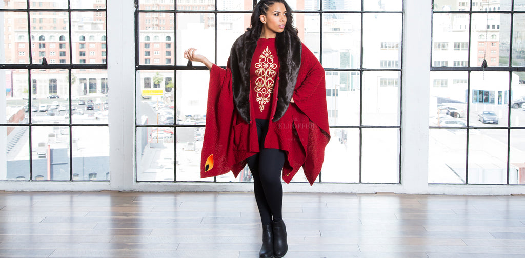 Malinda, a medium dark skinned model with dark hair, models the Galactic Queen Cape and Shell. The cape and the shell are the same scarlet red knit yarn. The shell has golden embroidery down the front and the cape has a black faux fur collar.