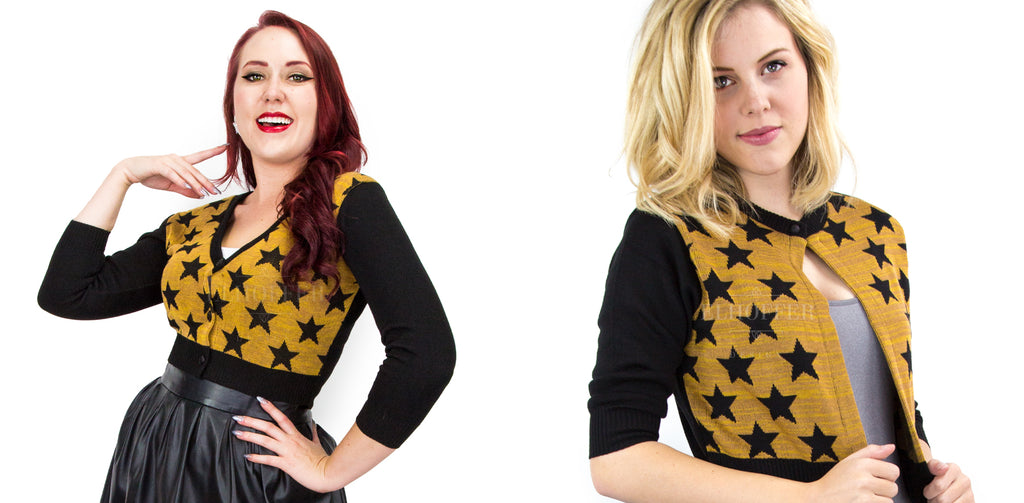 Two models standing on a white background. One wears the cardigan with a yellow body with black stars and sleeves buttoned up. The other wears an open front version of the cropped cardigan.