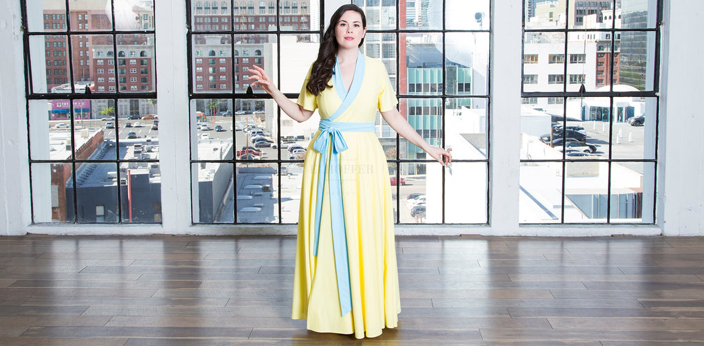 Devan (a fair skinned size medium model with long dark hair) models the Russian Princess Maxi Wrap Dress. The floor length dress with short flutter sleeves is light butter yellow, with a baby blue neckline and wrap belt at the waist.
