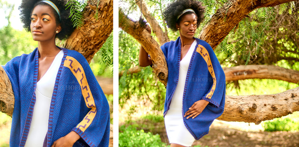 Armani (a tall and thin dark skinned model with black afro hair) models the Galactic Twilight Dolman over a white fitted dress. The dolman has an open front and is made from a blue knit with gold designs down the arms.