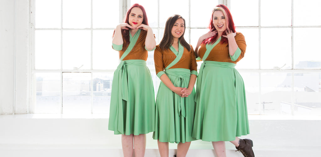Three models wear the Galactic Asset Wrap Dress. The dress has a copper brown top and sea foam green skirt.