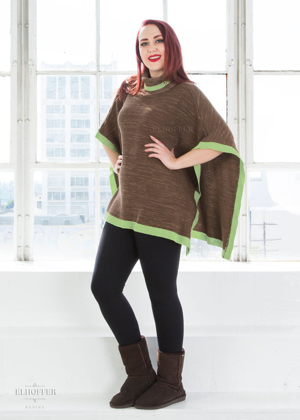 Kelsey models the multi shade brown poncho with mock turtleneck and green ribbed trim. It has opens sides and falls to the hips.
