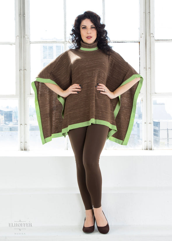 Kit models the multi shade brown poncho with mock turtleneck and green ribbed trim. It has opens sides and falls to the hips.