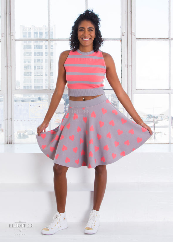 Ciara models a gray and pink striped sleeveless knit crop top and gray knit knee length skirt with pink hearts on it.