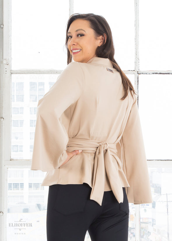 Kim models the sand colored wrap top with v neck, bell sleeves, and attached fabric belt.
