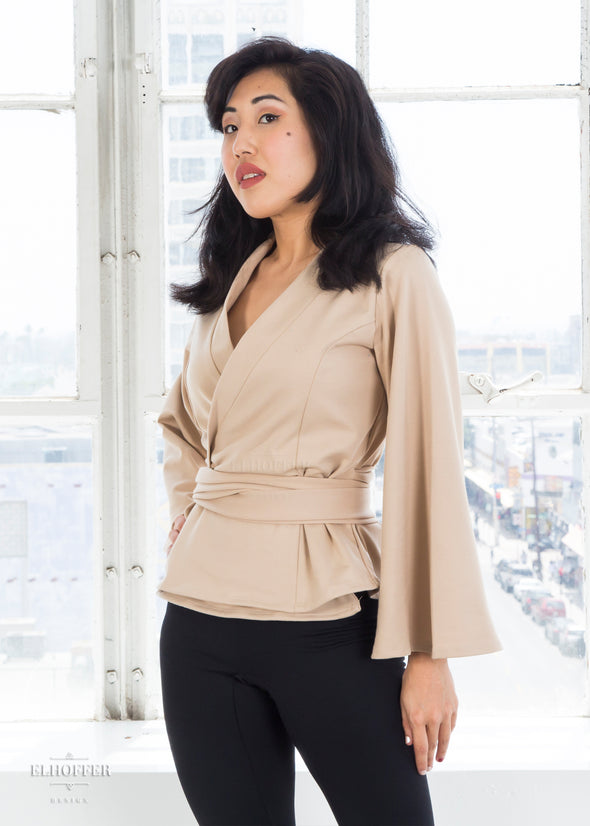 Kate models the sand colored wrap top with v neck, bell sleeves, and attached fabric belt.