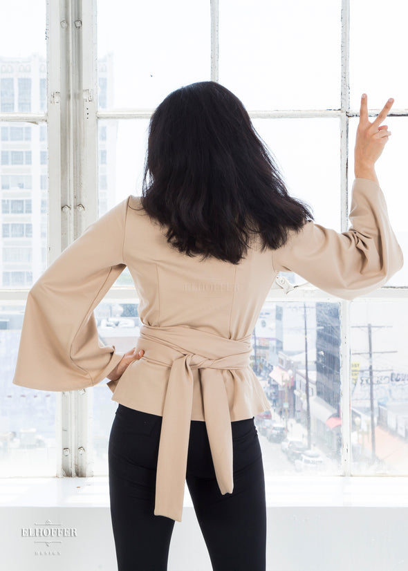 Kate is modeling the back of the sand wrap top, with the belt tied in the back.