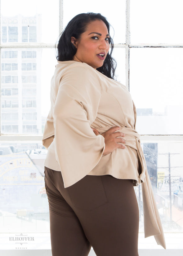 Tas models the sand colored wrap top with v neck, bell sleeves, and attached fabric belt.
