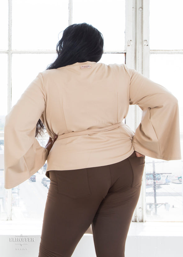 Tas models the back of the sand wrap top.