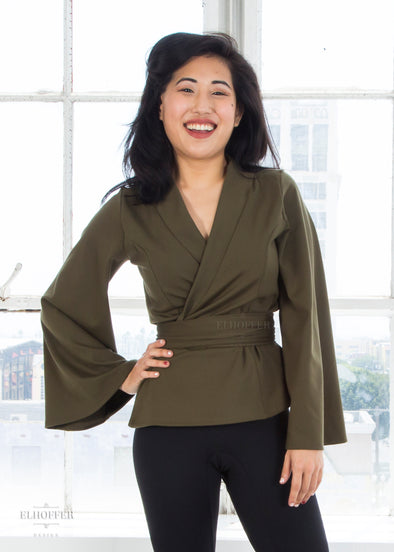 "Kate is modeling the XS olive wrap top. She has a 34"" Bust, 25"" Waist, 36"" Hip and is 5'2""."