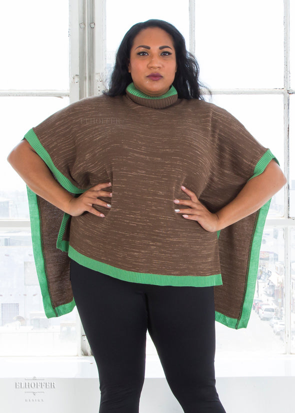 Tas models the multi shade brown poncho with mock turtleneck and green ribbed trim. It has opens sides and falls to the hips.