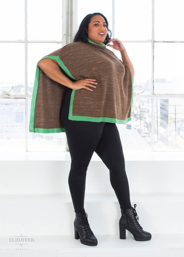 Tas pairs the poncho with a black tank top and our high waisted black leggings.
