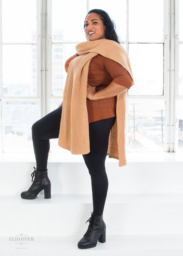 Tas models the tabard with the right poncho piece over her left shoulder, creating a scarf look.