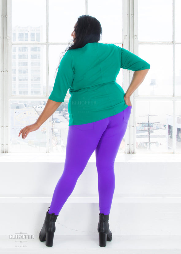 Tas shows the full size pockets of the purple high waisted leggings