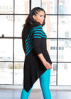 Malinda models the tunic which has 5 teal stripes from the right shoulder to the left hip and features a pocket on the front.