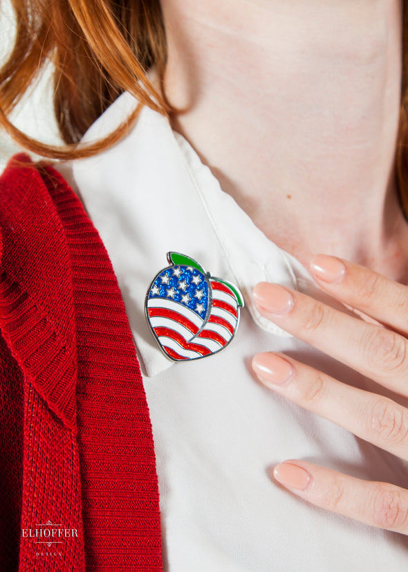 A close up of the pin, featuring glitter in the blue and red enamel of the American flag coloration of the peach.