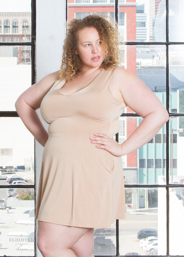 Anastasia models the caramel slip dress which has a low v neck, two small pockets, and a hem that falls to mid thigh. It is not meant as outerwear.