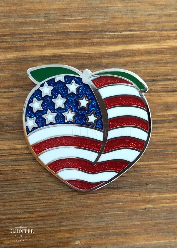 A nickel plated enamel pin in the shape of a peach with enamel American flag coloring, the red and blue include glitter.