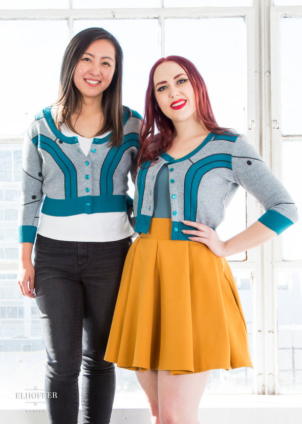 Alice and Kelsey model the gray and teal cropped cardigan with 3/4 sleeves and teal buttons.