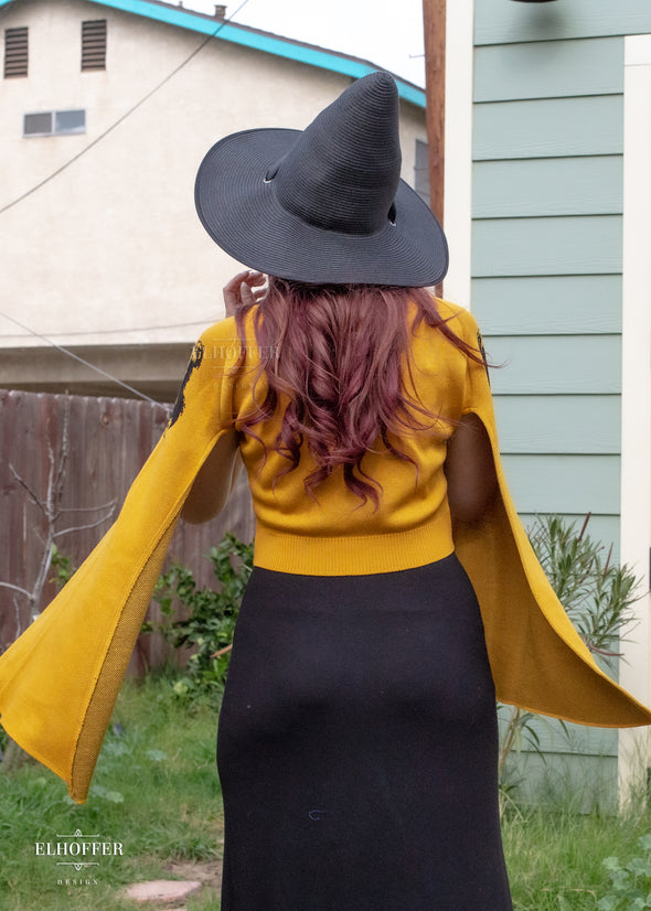 Kelsey pairs the yellow cropped cardigan with a black maxi and witchy hat.